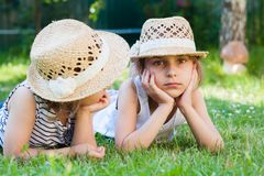 Sisters, two little girls on the grass, summertime, holidays. From school Stock Photo