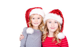 Sisters or two young girls wearing Santa hats Royalty Free Stock Photo