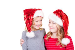 Sisters or two young girls wearing Santa hats Royalty Free Stock Image