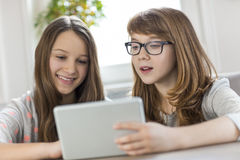 Sisters using digital tablet at table in house Royalty Free Stock Image