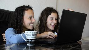 Sisters using laptop and smiling. Teenage girl and sister looking at laptop. Finishing successful project and making fun and joy while drink cold ice coffee stock video