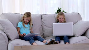 Sisters using laptop and tablet pc. On a sofa stock video footage