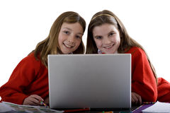 Sisters using laptop to do homework, cut out Royalty Free Stock Photography