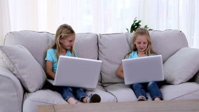 Sisters using laptops. On a sofa stock footage