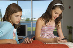 Sisters using their cell phones. Royalty Free Stock Images