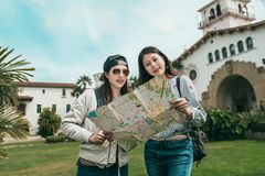 Sisters visiting beautiful building with guide map royalty free stock image