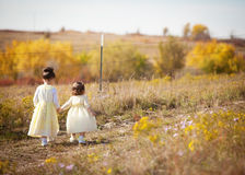 Sisters walking. Sisters holding hands and walking on path in country Stock Photography