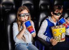 Sisters Watching 3D Movie At Theater. Sisters having snacks while watching 3D movie at cinema theater Royalty Free Stock Photo