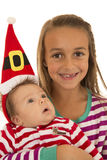 Sisters wearing pajamas and baby sister in a santa hat Stock Images