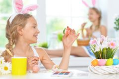 Portrait of sisters wearing rabbit ears decorating Easter eggs stock photos