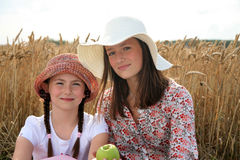 Sisters in wheat field. Two young sisters in floppy hats with apple sitting in wheat field Stock Photo