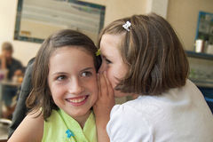 Sisters whispering on the ear Stock Photos