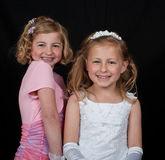 Sisters in white pink dress on black Royalty Free Stock Images