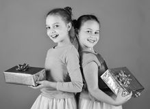 Sisters with wrapped gift boxes for holiday. Children open gifts for Christmas. Girls with smiling faces. Pose back to back with presents on green background royalty free stock photography