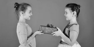 Sisters with wrapped gift boxes share presents for holiday. New Year presents concept. Children open gifts for Christmas. Girls with curious faces pose with stock photos