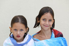 Sisters wrapped in a towel. Caucasian sisters with blue eyes wrapped in a beach towel just after having a swim Stock Photo