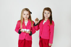 Sisters. Young twins with golf ball and bottle of perfume Stock Photos