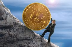 Sisyphus concept showing man struggling to push giant Bitcoin up a mountain representing goal of mining and getting rich Stock Photos