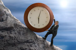 Sisyphus stressed for time man rolling huge clock up hill. Sisyphys metaphor showing a man struggling to roll a giant clock up hill representing deadlines, time Stock Photos
