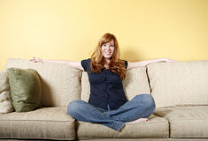 Sit next to me. Attractive red haired woman sitting on a sofa with arms outstretched Royalty Free Stock Images