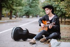 Sit and play music. On classic guitar in the park stock photography