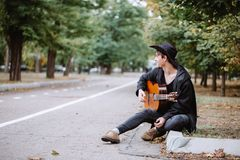 Sit and play. Musik in tha park autumn day royalty free stock image