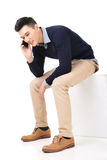 Sit and take a call. Handsome Asian guy sit and take a call, full length portrait isolated on white background Stock Image