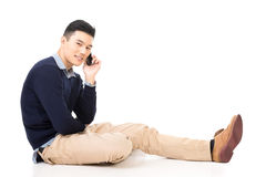Sit and take a call. Handsome Asian guy sit and take a call, full length portrait isolated on white background Royalty Free Stock Photography