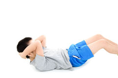 Sit up boy. Young asian boy workout his abs muscle by sit up on white background stock photo