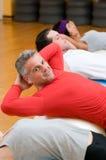 Sit-upsübungen an der Gymnastik Stockfotos