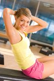 Sit-ups. Portrait of healthy woman doing sit-ups looking at camera with smile in the sports gym Stock Photography