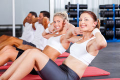 Sit ups. Fitness people doing sit ups in gym Stock Image