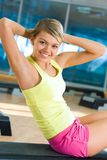 Sit-ups. Portrait of healthy woman doing sit-ups looking at camera with smile in the sports gym Royalty Free Stock Photo