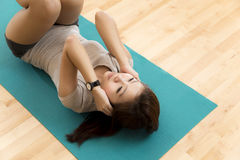 Sit ups. An Asian lady doing her sit ups execrise in a gym Royalty Free Stock Images