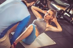 Sit-ups. Close up. Coach assisting young women doing sit-ups at a gym. Focus is on woman Royalty Free Stock Photos
