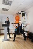 Sit-ups with electric stimulation. Caucasian women makes sit-ups with rod in gym. Female trainer standing behind manages electric muscle stimulation purposed to Stock Photos