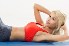 Sit-ups Exercise. Cute young woman exercising sit-ups. Looking at camera. White background Stock Images