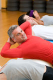 Sit-ups exercises at gym. Healthy people with mature instructor doing sit-ups on fitness ball at gym Stock Photos