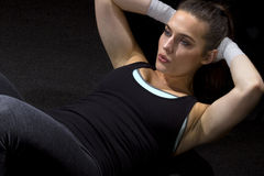 Sit Ups. Fit woman doing situps on a black background Royalty Free Stock Photography