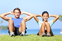 Sit ups - fitness couple exercising sit up outside. In grass in summer. Fit happy people working out cross training. Beautiful young multiracial couple, Asian Stock Image