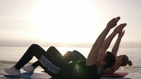 Sit ups - fitness couple exercising sit up outside in front thesea or ocean in summer. Fit happy people working out. Cross training. Beautiful young caucasian stock footage