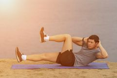 Sit ups - fitness man exercising sit up outside in grass in summer. Fit male athlete working out cross training in summer. Caucasian muscular sports model in Stock Photography