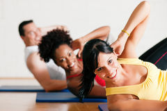 Sit-ups in gym for fitness. Group of three people exercising doing sit-ups in the gym for better fitness Stock Photography