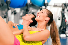 Sit-ups in gym for fitness. Two people, man and woman, exercising doing sit-ups in the gym for better fitness Stock Photography