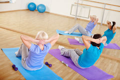 Sit-ups. Mature females doing sit-ups on mats in sport gym Royalty Free Stock Photos