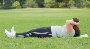 Sit ups. Obese woman sit ups on grass Stock Photos