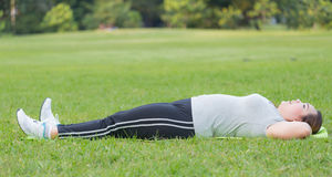 Sit ups. Obese woman sit ups on grass Royalty Free Stock Photos