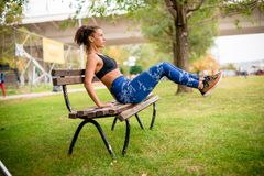 Sit-ups on park bench. Young female athlete doing sit-ups on park bench Royalty Free Stock Images