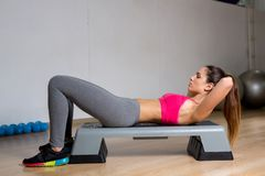 Sit-ups. Sporty female making sit-ups during workout on special equipment in gym Royalty Free Stock Photos