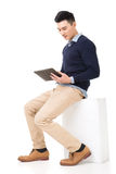 Sit and use pad. Handsome Asian guy sit and use pad, full length portrait isolated on white background Royalty Free Stock Image
